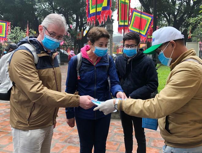 Khách du lịch đeo khẩu trang phòng virus corona, khám phá Thủ đô Hà Nội Ảnh 4