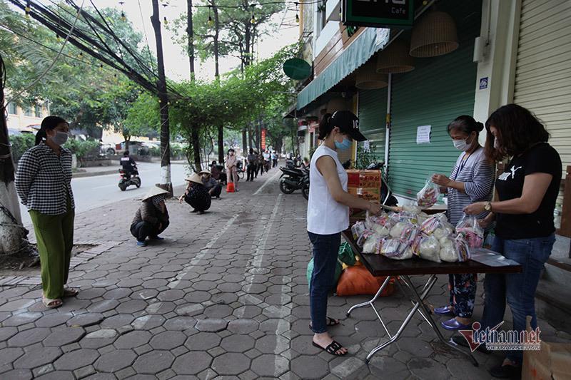 Nón, dép xếp thẳng hàng cách nhau 2m của người dân nhận thực phẩm miễn phí Ảnh 1