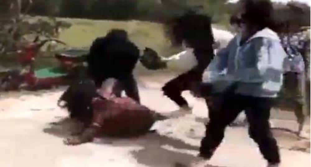 Đoạn clip dài gần 5 phút quay lại cảnh một nhóm nữ sinh dùng nón bảo hiểm  và mũ cối đánh tới tấp vào một bạn nữ khác.