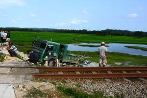 Xe tải cắt đầu bị tàu hỏa tông xuống ruộng