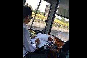 Tài xế xe khách vừa lái xe vừa ghi chép sổ