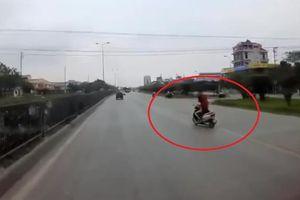 Đang chở con nhỏ, người phụ nữ buông tay lái cởi áo mưa
