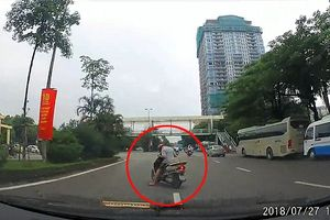 Người đàn ông đi xe máy ngủ gục giữa đường phố đông đúc