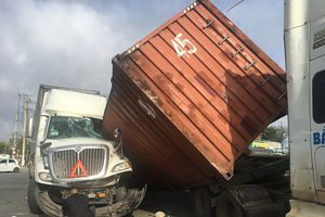 Thùng container bật khỏi giá đỡ rơi trúng một xe container khác, tài xế mắc kẹt trong cabin
