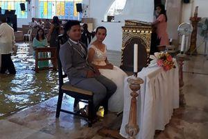 Bất chấp mưa bão xối xả, cặp đôi đi thuyền tới nhà thờ ngập nước để tổ chức đám cưới