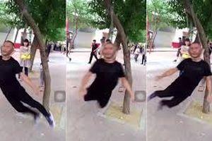 Người đàn ông tập thể dục bằng cách treo cổ lên cây rồi xoay như chong chóng