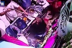 Nữ nhân viên bán hàng cầm chổi chống lại tên cướp có súng
