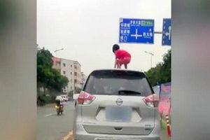 Thót tim bé gái trèo qua cửa sổ trời, đứng nhảy trên nóc ô tô đang chạy