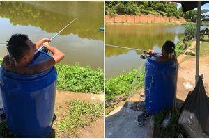 Nhiệt độ thực tế ngoài trời lên đến 50 độ C, người đàn ông vừa ngâm mình trong thùng phuy đầy nước vừa câu cá tận hưởng cuộc sống