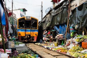 Chợ đường sắt tấp nập du khách khi tàu hỏa chạy qua ở Thái Lan