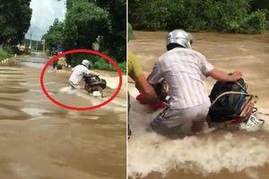 Liều lĩnh dắt xe máy qua lũ xiết, người đàn ông suýt bị cuốn trôi