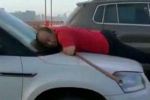 Nữ tài xế để nhân viên vệ sinh vật vã bám trên nắp ca pô chạy 13km mới dừng