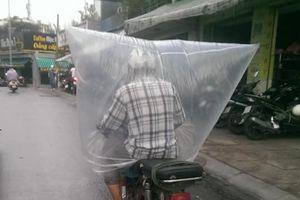 Không có áo mưa, người đàn ông trùm bao nylon kín mít khi chạy xe