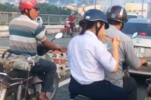 Vội đi học, nữ sinh tranh thủ ăn nguyên tô mỳ sau yên xe máy khiến nhiều người chạnh lòng