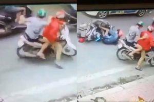 Người phụ nữ đang đi xe máy bất ngờ bị hai gã đàn ông áp sát đạp ngã sõng xoài ra đường