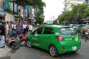 Taxi Mai Linh tông nhiều xe gắn máy đang dừng đèn đỏ