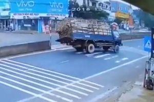 Cụ ông đạp xe sang đường khiến xe tải chở gỗ lật nhào