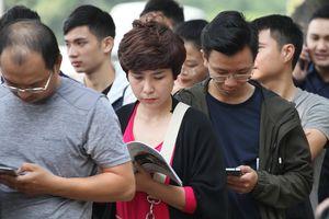 Người dân thong thả đọc sách, lướt web trong lúc chờ nhận vé trận Việt Nam - Philippines