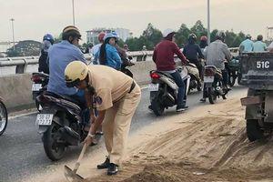 Cảnh sát giao thông cùng người dân dọn cát rơi trên đường ở Sài Gòn