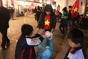 Trẻ em dọn rác trên phố trung tâm Hà Nội sau khi người hâm mộ 'đi bão' mừng Việt Nam vô địch