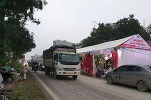 Rạp cưới dựng giữa quốc lộ, xe ben, xe tải vun vút lao qua