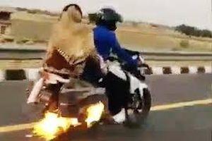 Người đàn ông chở vợ con trên chiếc xe máy bốc cháy
