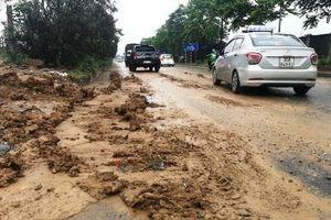Đội mưa dọn dẹp bùn đất trên Đại lộ Thăng Long