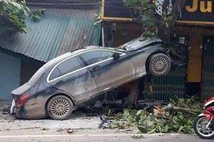 Mercedes mất lái, leo lên cây ven đường