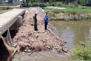 Dân thuê xe đổ đất chặn dòng kênh bị nhuộm đen