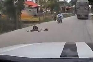 Người đàn ông say xỉn nằm lăn ra giữa đường đầy xe cộ