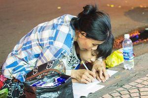 Bức ảnh mẹ dạy con học bài trên vỉa hè khiến nhiều người xúc động