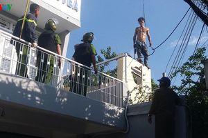 Gần 100 cảnh sát xịt vòi rồng khống chế thanh niên cầm dao trên nóc nhà