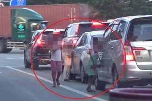 Trẻ em bám vào ôtô gõ cửa để xin tiền ở Sài Gòn