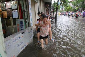 Hà Nội: Mưa lớn từ sáng sớm, người dân 'bì bõm' đưa con đi học, đi làm