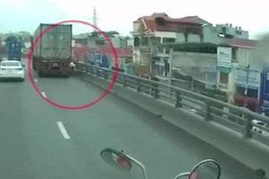 Đi vào đường cấm, xe máy may mắn thoát chết dưới bánh xe container