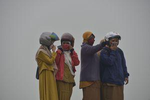 Người đeo khẩu trang, máy bay lăn bánh giữa bụi mù cháy rừng Indonesia