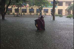 Phụ huynh bì bõm cõng con giữa trời mưa như trút ở thành Vinh