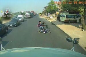 Sang đường trước đầu container, 2 học sinh đi xe đạp điện suýt bị tông trúng