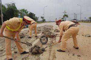 Xe tải làm rơi bùn đất ngập đường, CSGT vất vả hót dọn