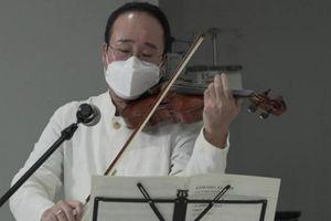 Nghệ sĩ đeo khẩu trang, chơi violin an ủi bệnh nhân COVID-19