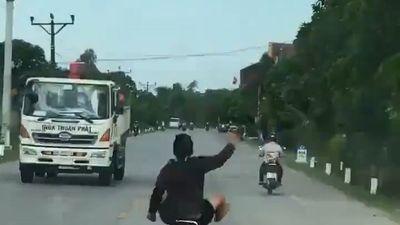 Thanh niên vác chân lên xe, vừa chạy vừa múa tay trên đường