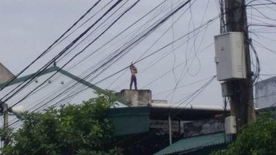 Hoảng hồn với video người đàn ông bế cháu bé di chuyển trên nóc nhà
