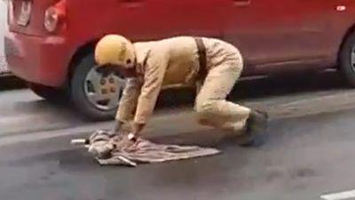 Nam cảnh sát lau dầu loang để người đi đường không bị trượt