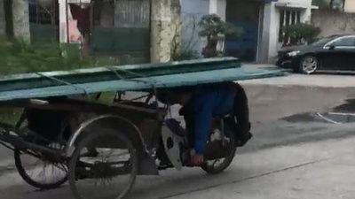 CLIP: Người đàn ông nằm úp bụng lên yên, chở 'máy chém' chạy vi vu ngoài đường