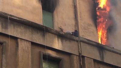 Cận cảnh người đàn ông nằm trên gờ tường thoát khỏi đám cháy