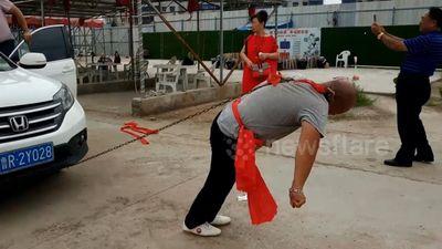 Cao thủ kungfu Trung Quốc dùng một tai kéo hai ô tô chở đầy người