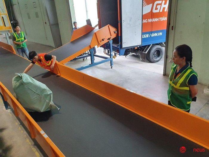 Các túi đầy sẽ được nhân viên chuyển ra bằng chuyền, đưa lên xe tải giao hàng. Ảnh: Hải Đăng
