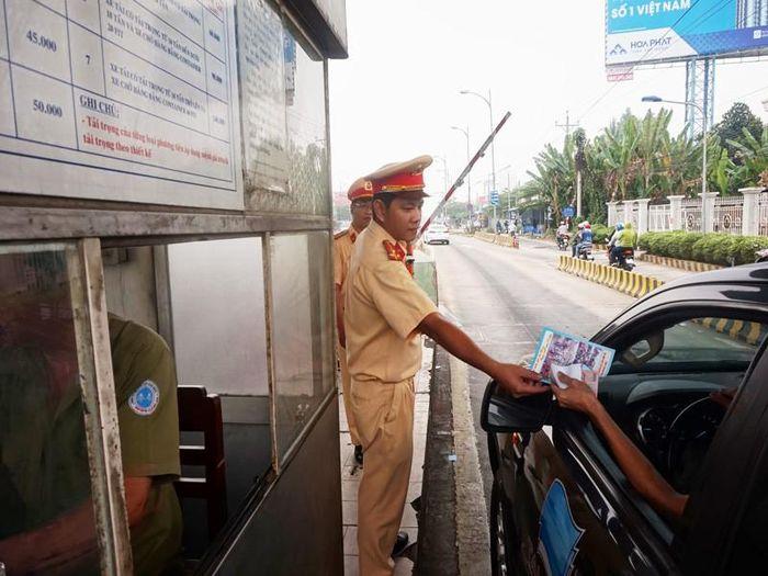 CSGT phát tờ rơi cho tài xế tại trạm thu phí cầu Rạch Miễu